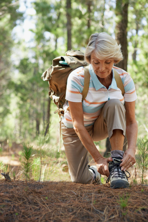 Senior Woman Tying the Laces of Her Walking Boots in Woodland During a Hike