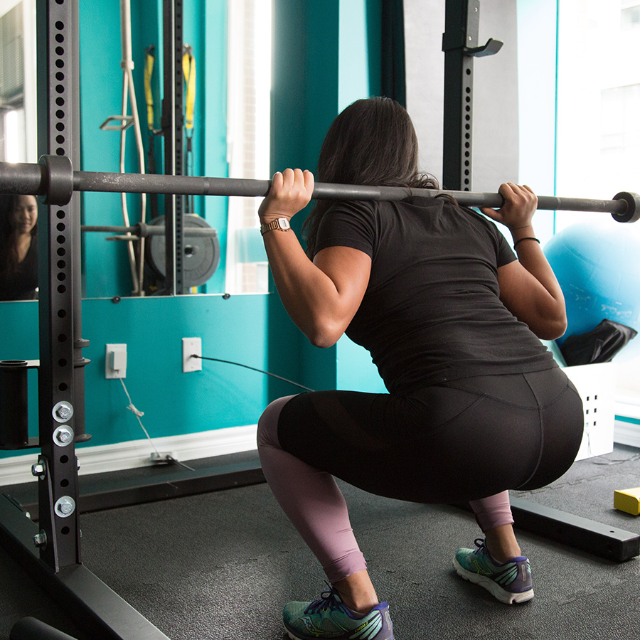 Woman doing squats with bar