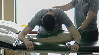 Client learning stretching techniques with chiropractor