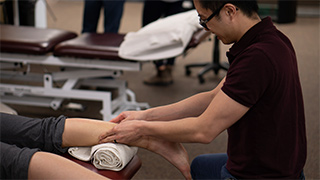 Physiotherapist treating client foot