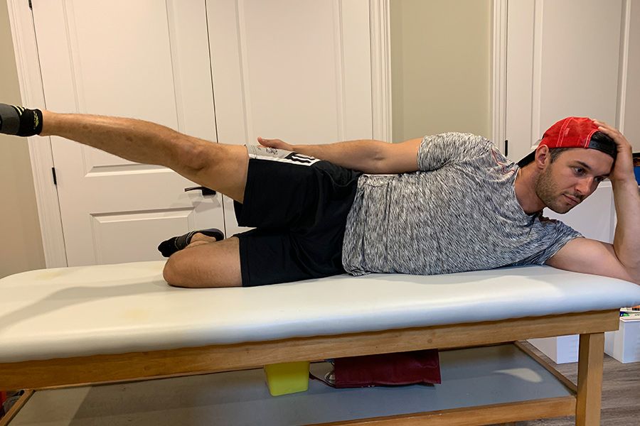 male on physio table doing side laying hip abduction exercise