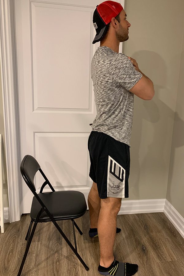 male standing in front of chair