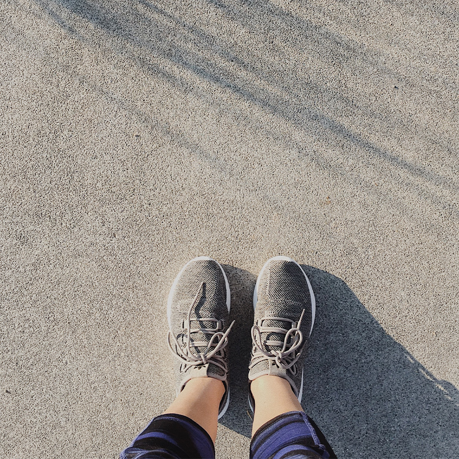 feet in running shoes on pavement