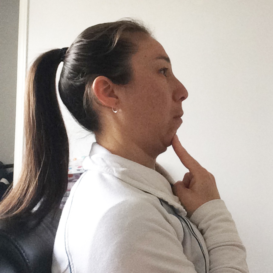 Female sitting tall to demonstrate chin tuck exercise