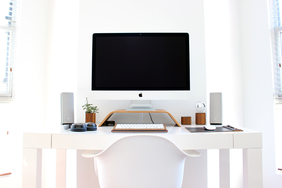 desk with white chair and mac screen