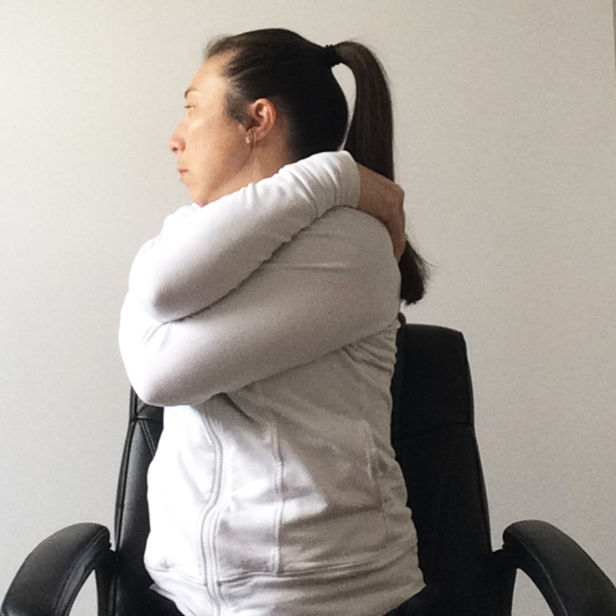 female sitting in chair holding neck for spine twist stretch