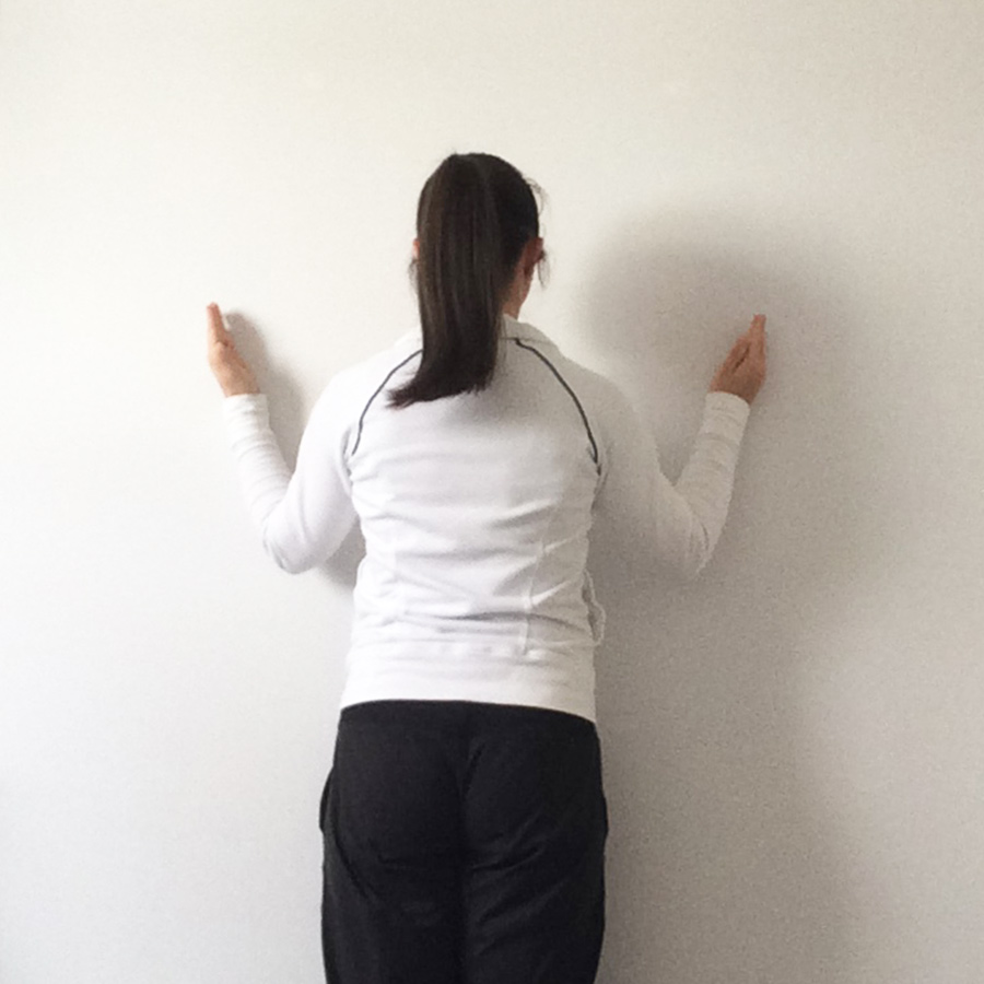 female standing facing wall demonstrating wall slide exercises