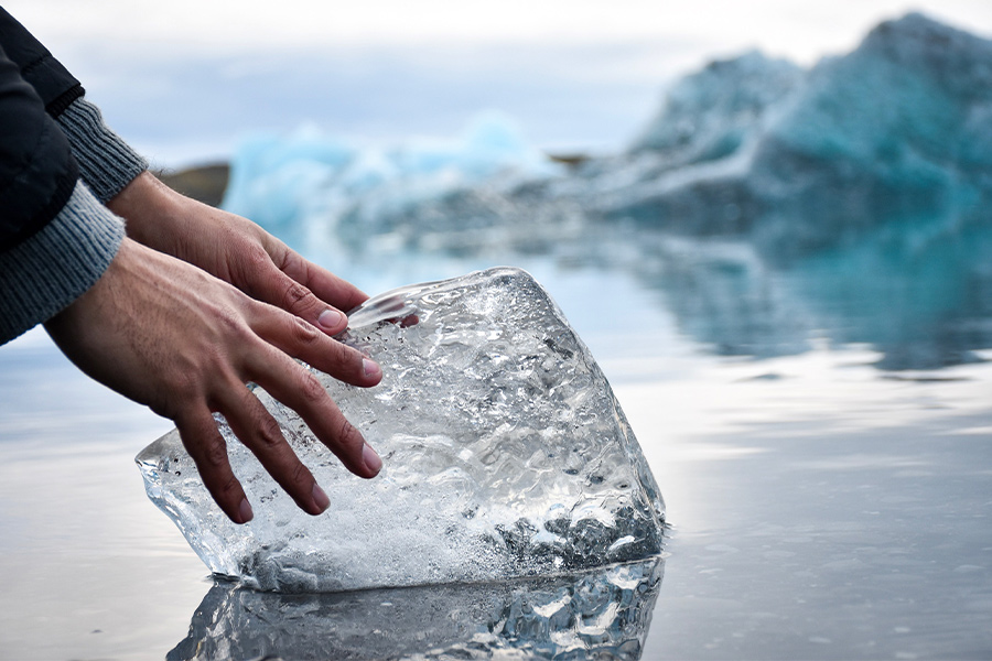 hands holding piece of ice in water