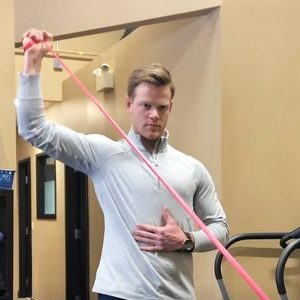 Man demonstrating shoulder exercises with red tension band