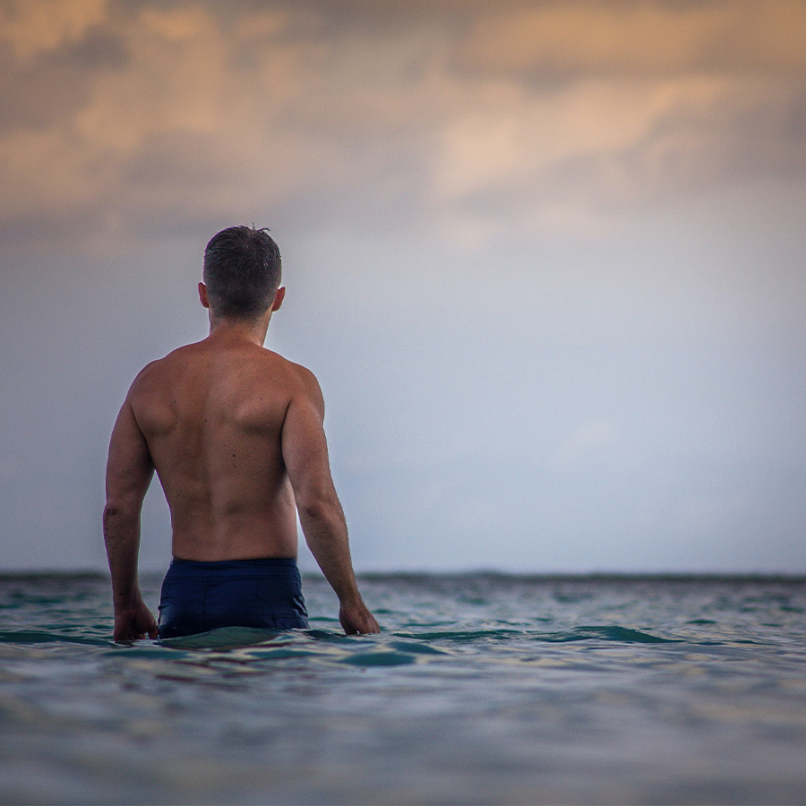 man from behind looking out on water horizon