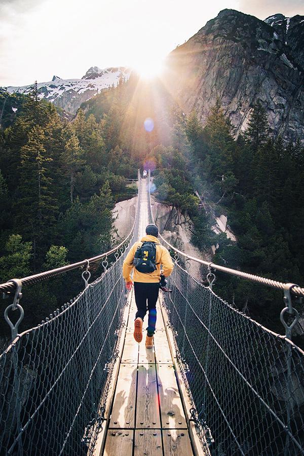 Person walking on bridge through mountains