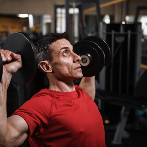 Athletic male doing shoulder exercise with dumbells.