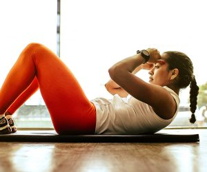Female doing sit ups on yoga mat