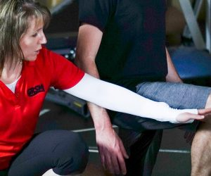 physiotherapist demonstrating lower extremity exercise